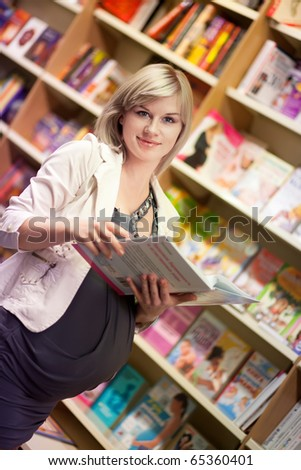 Pregnant woman with book at bookshop - stock photo