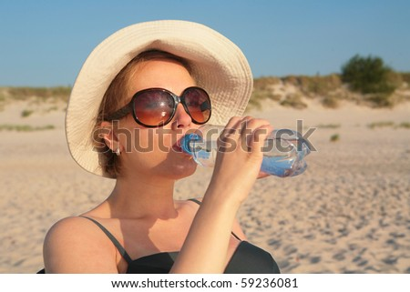 Pregnant woman with bottle of water on sea beach - stock photo