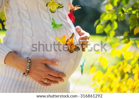 Pregnant woman with butterflies on her belly, outside in a park - stock photo