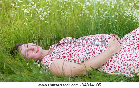 Pregnant woman with closed eyes lie in chamomile and grass background - stock photo