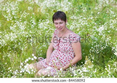 Pregnant woman with closed eyes sitting in chamomile background - stock photo