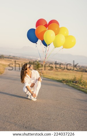 Pregnant woman with colorful ballons in her hand on the road - stock photo