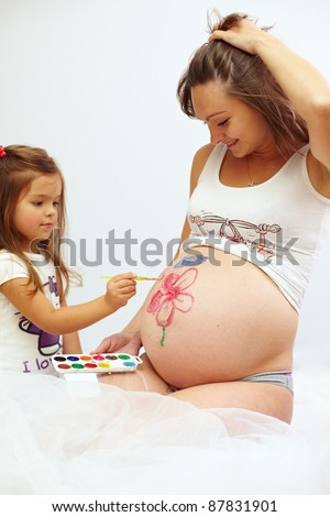 pregnant woman with cute daughter paint mom?s belly - stock photo
