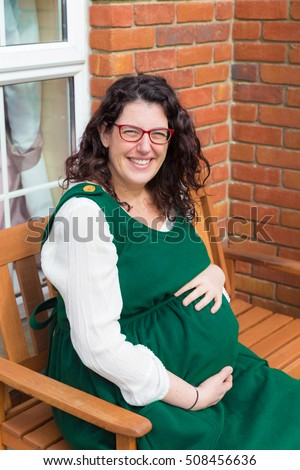 Pregnant woman with glasses wearing a green maternity dress and holding her pregnant tummy with a big smile sitting in front of her house on a wooden bench
