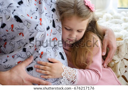 Pregnant woman with her daughter. Child girl hugging his pregnant mother