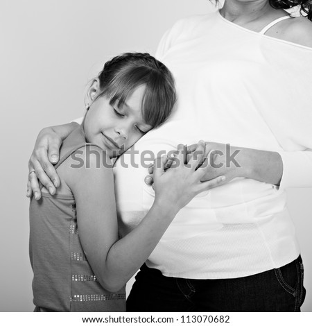 Pregnant woman with her daughter studio shooting. black-white image - stock photo