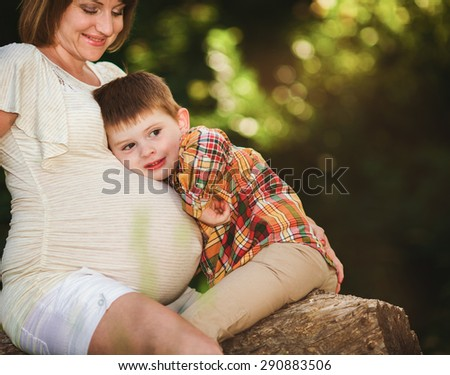 Pregnant woman with her eldest son spending time outdoor - stock photo
