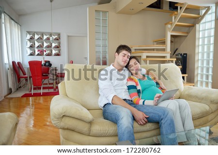 pregnant woman with her husband have fun relax and using tablet comture at modern home - stock photo
