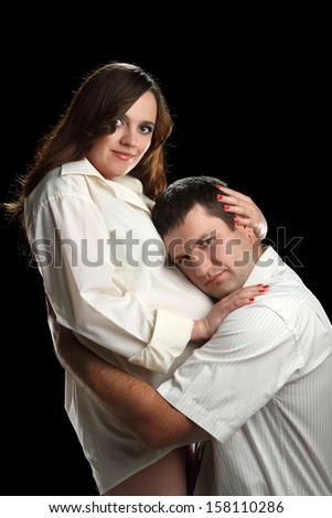 pregnant woman with her husband in the studio - stock photo
