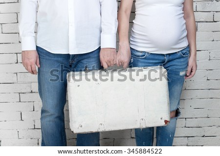 Pregnant woman with her husband standing against a white wall with a white suitcase - stock photo