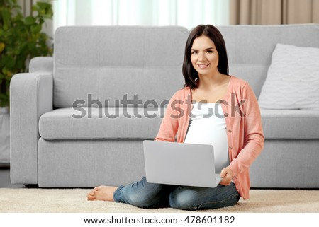 Pregnant woman with laptop sitting on floor