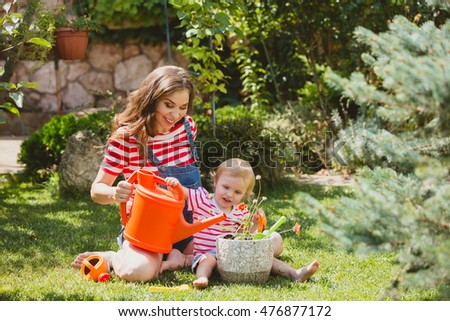 Pregnant woman with little daughter in the garden.