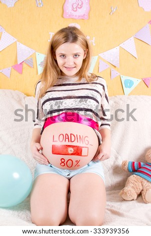 Pregnant woman with loading concept painted on her belly. - stock photo
