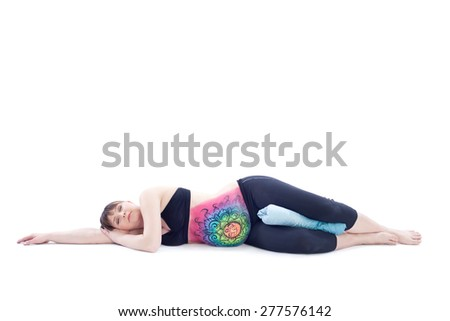 Pregnant woman with painted belly doing yoga exercise - stock photo