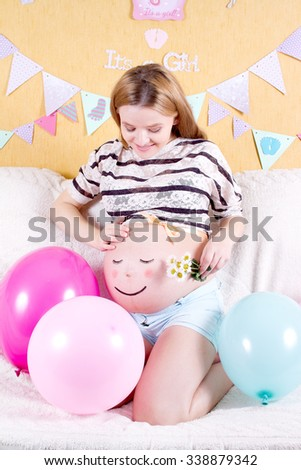 Pregnant woman with painted eyes on his stomach and mouth - stock photo