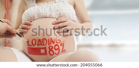 pregnant woman with painted husband on paints watercolor brush word  loading and figures 89% idea of creativity in stage of uterine development forward long awaited child Copy space for inscription