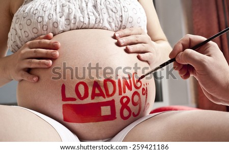 pregnant woman with painted husband on paints watercolor brush word - loading and figures 89% idea of creativity in stage of uterine development, looking forward to long awaited child Against window - stock photo