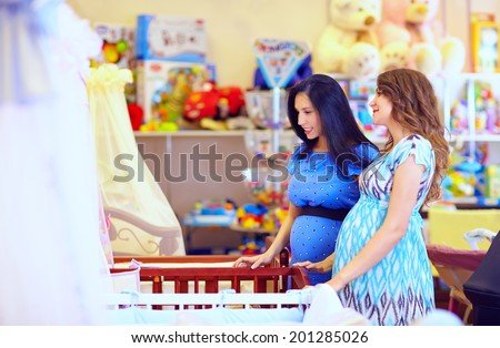 pregnant women choosing cot for baby - stock photo