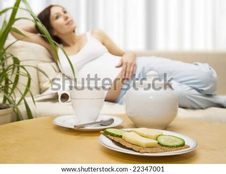 Pregnant young brunette lying on a bed before breakfast