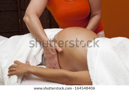 Pregnant young latina woman with beautiful skin, being wrapped with a towel, lying on a bed and having a relaxing prenatal massage, various techniques - stock photo
