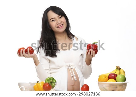 Pregnant Young Woman Cooking vegetables  Healthy Food - Prepare Vegetable Salad Healthy Food Concept on the white background. - stock photo