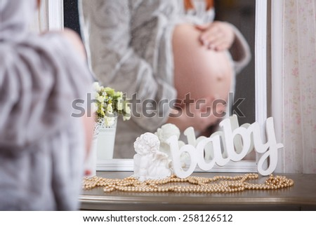 "pregnant young woman in soft fluffy bathrobe pregnant girl tenderly embraces his tummy wooden decoration handmade word ""baby"" - stock photo"