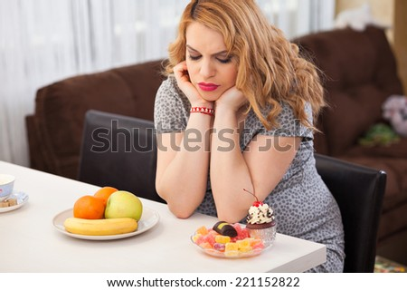 Pregnant young woman trying to decide whether to eat fruits or sweets, sitting at the kitchen table - stock photo