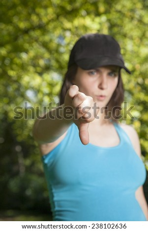 pregnant young woman with blue shirt black cap thumb down over green trees background street - stock photo