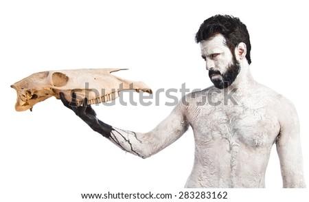 prehistoric man looking horse skull - stock photo