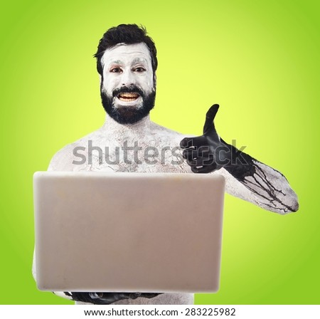 Prehistoric man with laptop over colorful background - stock photo