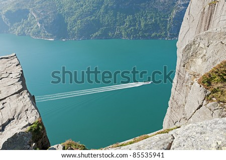 Preikestolen boat on the green water of fjord Norway - stock photo