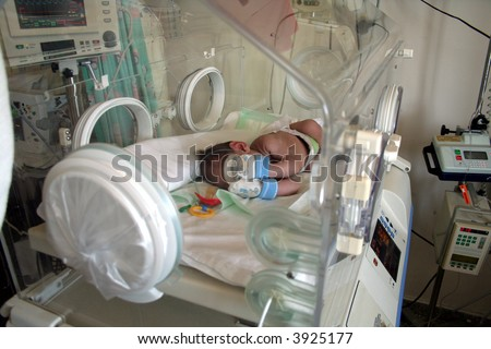Premature baby in incubator - stock photo