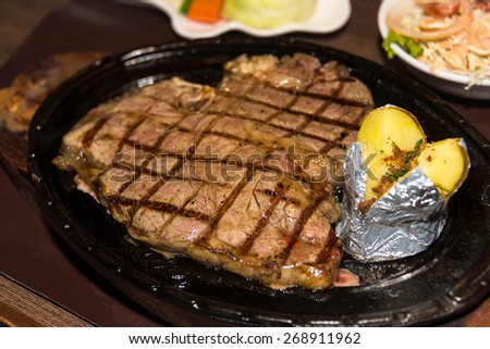 Premium American prime rib steak on a metal plate ready to serve. The focus is shallow depth of field. - stock photo