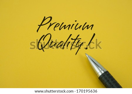 Premium Quality note with pen on yellow background