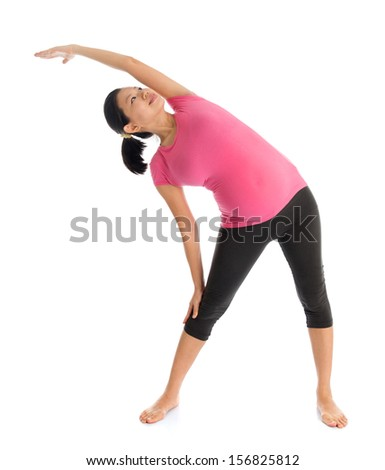 Prenatal yoga class. Full length healthy Asian pregnant woman doing yoga exercise stretching, full body isolated on white background. Yoga positions standing side stretch. - stock photo