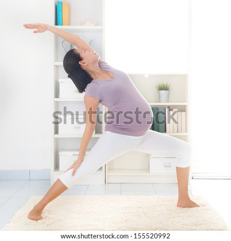 Prenatal yoga class. Full length healthy 8 months pregnant calm Asian woman meditating or doing yoga exercise at home. Relaxation and stretching. - stock photo