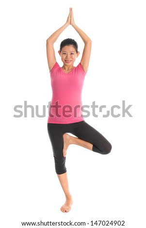 Prenatal yoga. Full length healthy Asian pregnant woman doing yoga exercise stretching at home, full body isolated on white background. Yoga positions standing tree pose. - stock photo