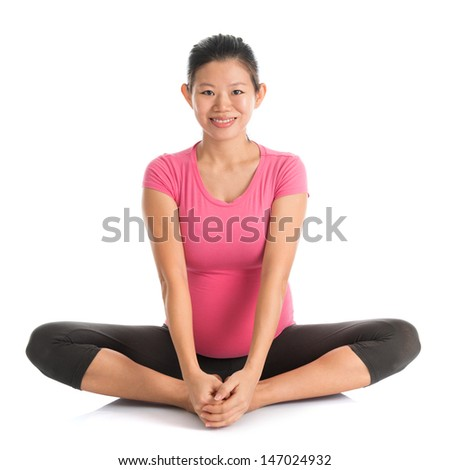 Prenatal yoga. Full length healthy Asian pregnant woman doing yoga exercising stretching, full body isolated on white background. Yoga butterfly pose. - stock photo