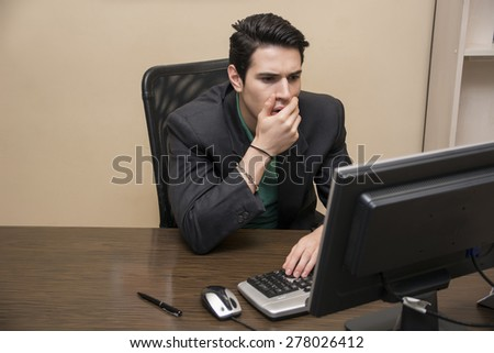 Preoccupied, worried, desperate young male worker staring at computer screen in his office - stock photo