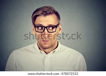 Preoccupied worried man in unpleasant, awkward situation isolated on gray background. Negative emotions facial expression