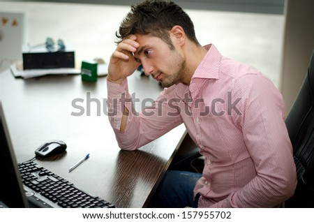 Preoccupied, worried young male worker staring at computer screen in his office - stock photo