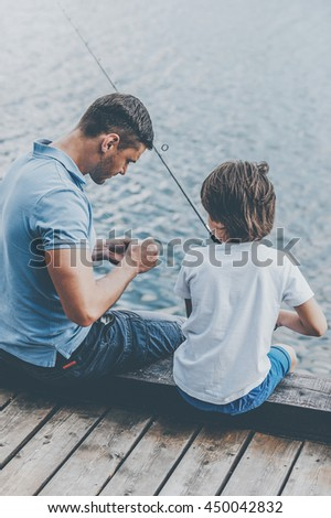 Preparation before fishing. Rear view of father and son sitting at the quayside and preparing fishing rod for fishing - stock photo