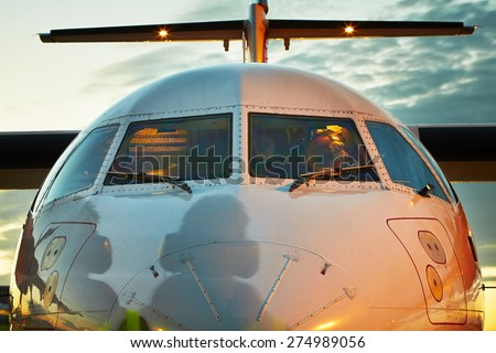 Preparation before take off - Cockpit of the airplane and shadow of the ground crew - stock photo
