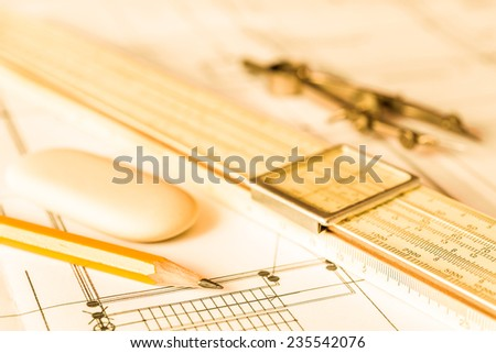 Preparation for drafting papers, the tools and schemes on the table. Angle view, focus on a pencil, in yellow tone - stock photo