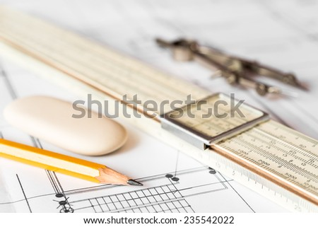 Preparation for drafting papers, the tools and schemes on the table. Angle view, focus on a slide rule - stock photo