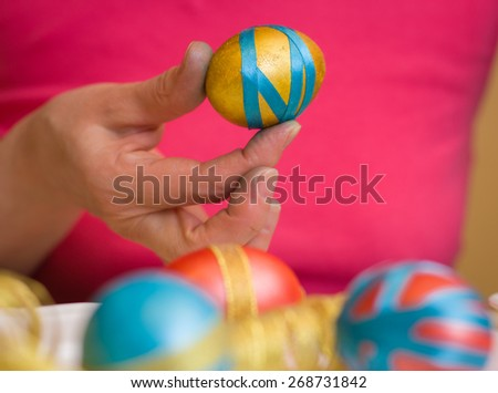 Preparation for Easter. Female hands closeup decorate Easter eggs. - stock photo