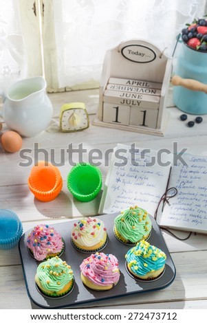 Preparation for tasty muffins with cream and decoration - stock photo