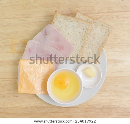 preparation fresh eggs ,bacon ,cheese and bread with butter in dish