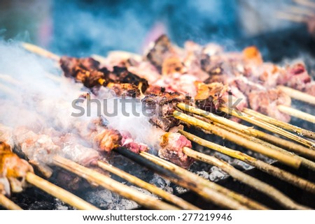 Preparation of barbecue on grill. Roasted meat slices shashlik. Selective focus and shallow DOF - stock photo