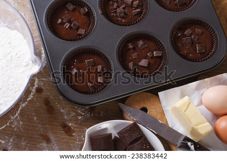 preparation of chocolate muffins close-up on the table. horizontal view from above  - stock photo